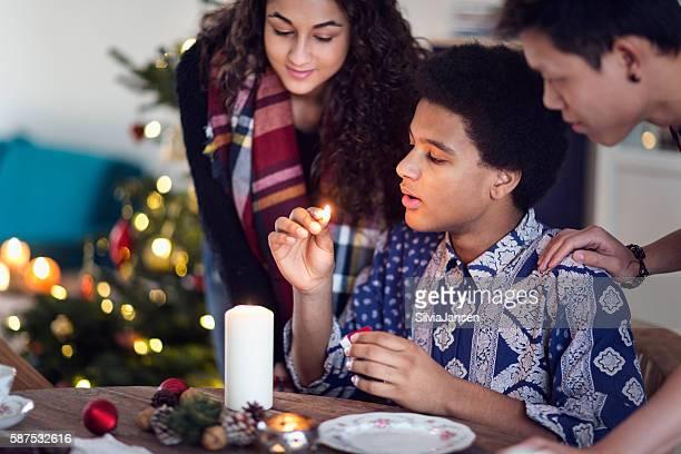 young people celebratin christmas lighting candle