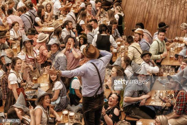 young people celebrating in beer pavilion on oktoberfestfest in munich - oktoberfest stock pictures, royalty-free photos & images