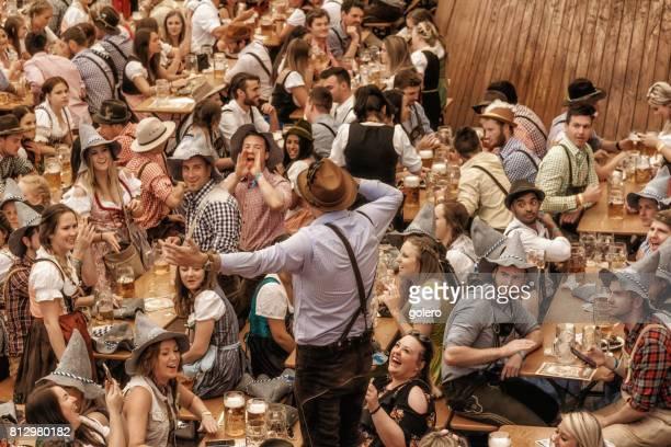 jovens, celebrando no pavilhão da cerveja em oktoberfestfest em munique - munique - fotografias e filmes do acervo