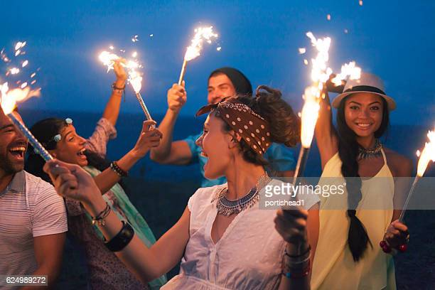 Young people celebrating with fireworks on beach