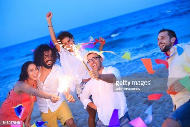Jeunes gens célébrer avec des feux d'artifice sur la plage