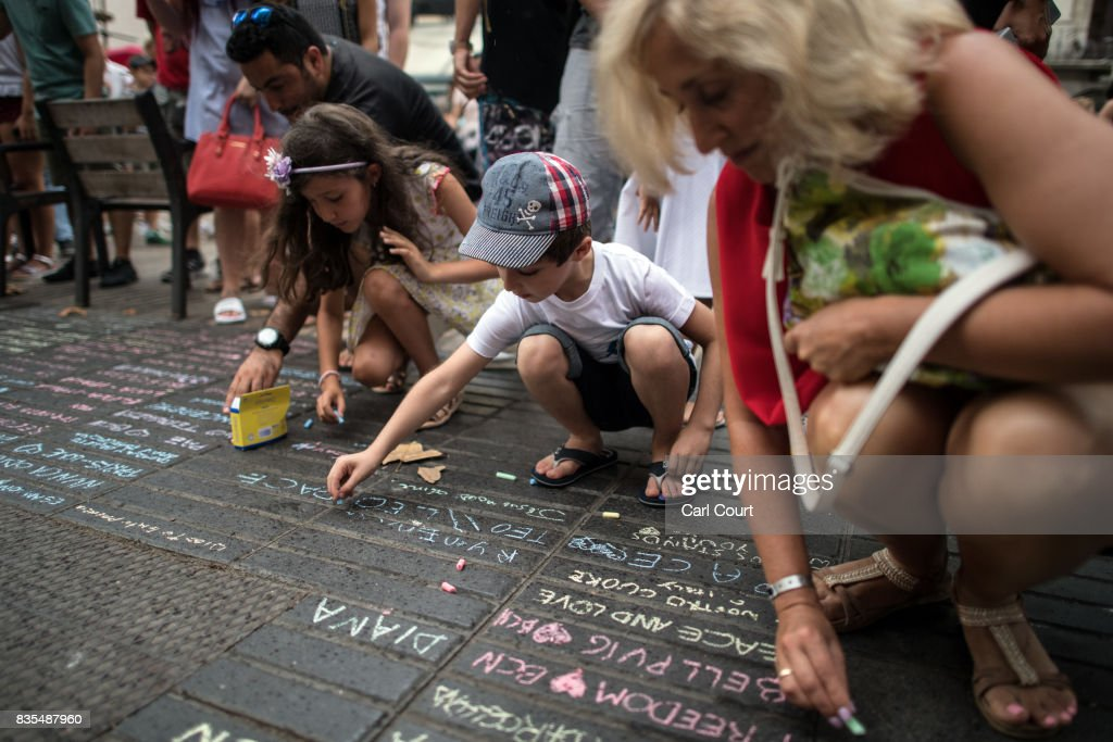 Young people chalk messages on the ground on Las Ramblas near the scene of Thursday's terrorist attack, on August 19, 2017 in Barcelona, Spain. A nationwide manhunt continues for Younes Abouyaaqoub, now named by Spanish media as the suspected driver in an attack that left thirteen people dead and dozens injured when a van was driven at crowds in the popular Las Ramblas area of Barcelona on Thursday.