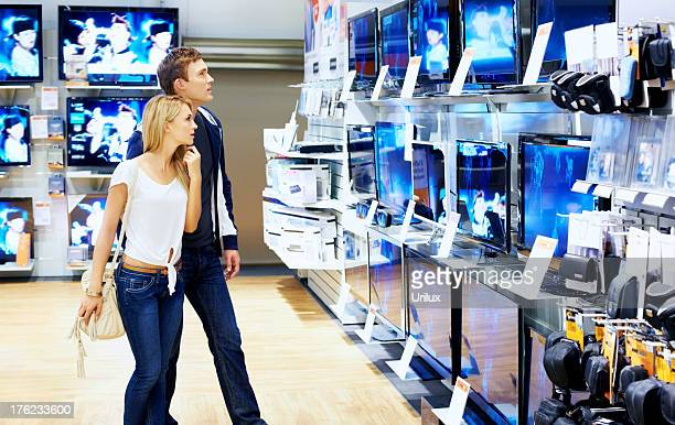 Young people checking out new television sets in megastore