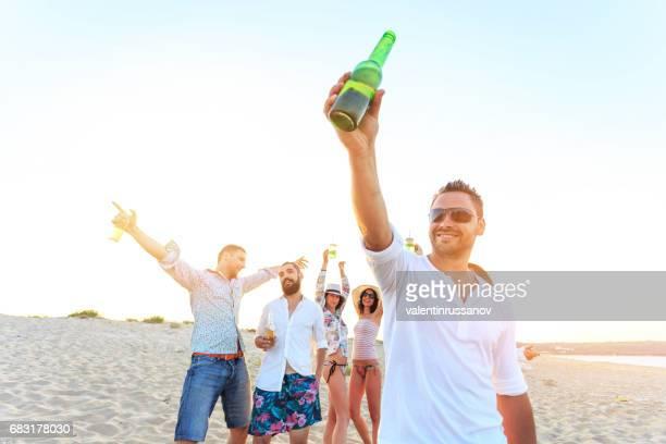 young people cheering on beach - comemoração conceito imagens e fotografias de stock