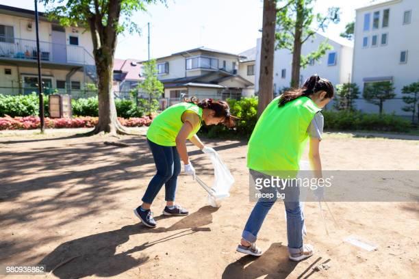 若い人は公共の公園を清掃