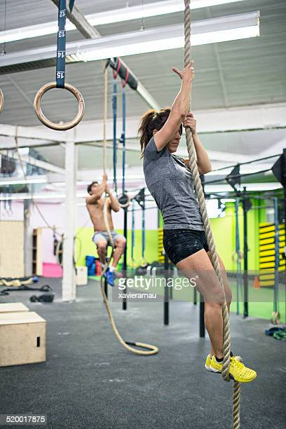 Young people climbing ropes in the gym