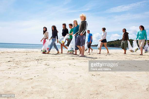 young people collecting garbage on beach - helena price stock-fotos und bilder
