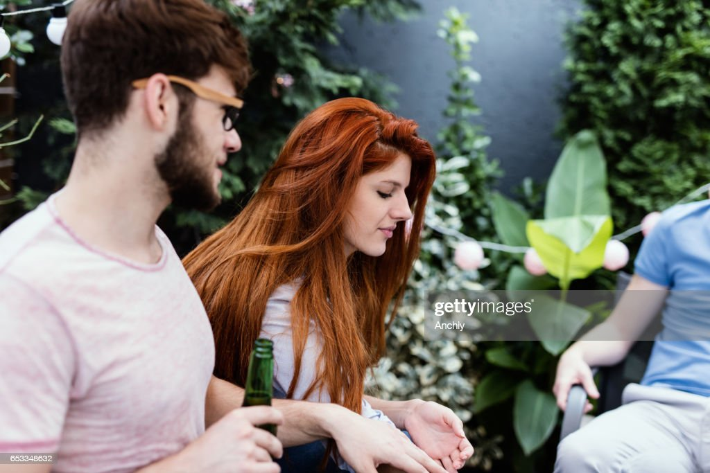Young People communicating in cafe outdoors. Friends hanging out : Stock Photo