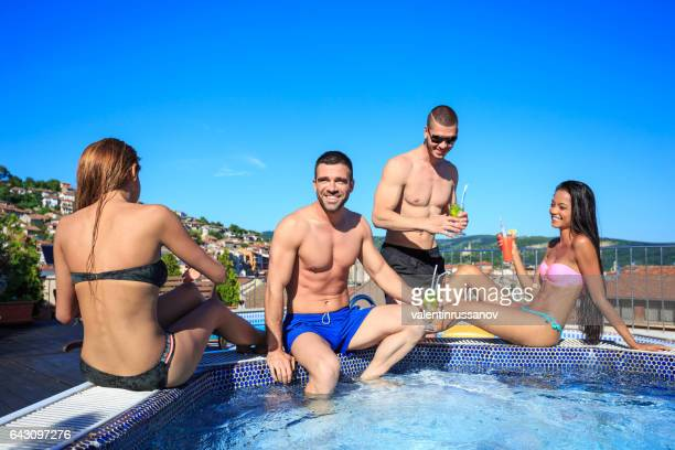 Young people drinking cocktails on rooftop swimming pool