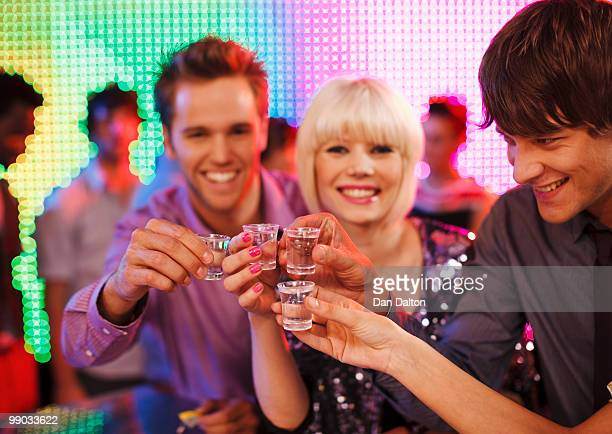 Young people drinking tequila shots in a nightclub
