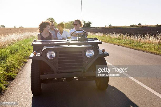 Young people driving in old military Jeep