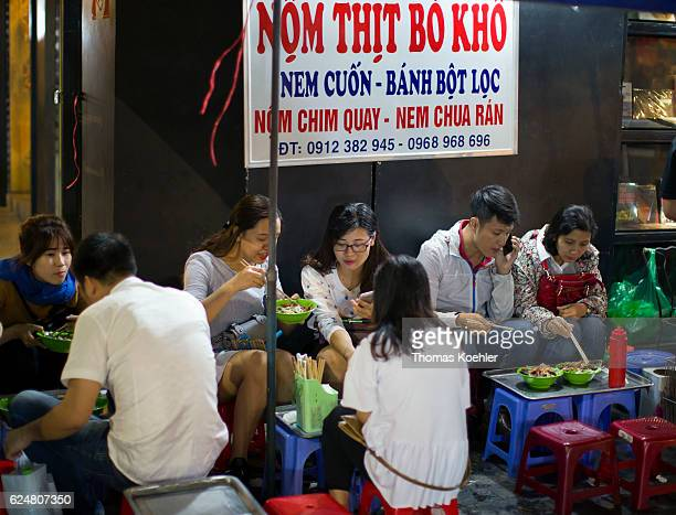 Young people eat at a snack bar on a street in Hanoi on October 30 2016 in Hanoi Vietnam