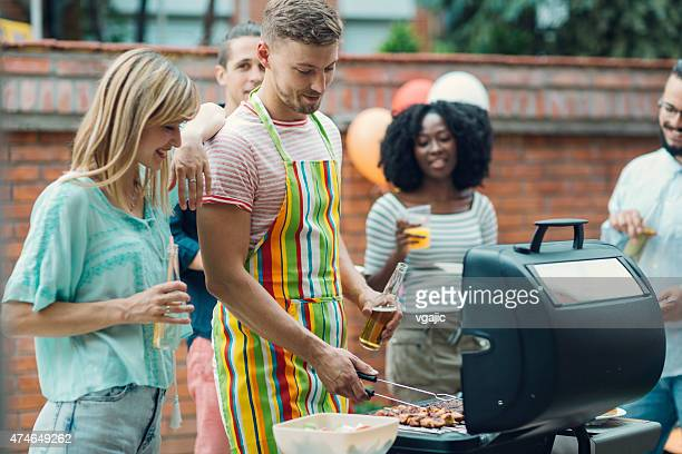 Young People Eating At Barbecue Party.