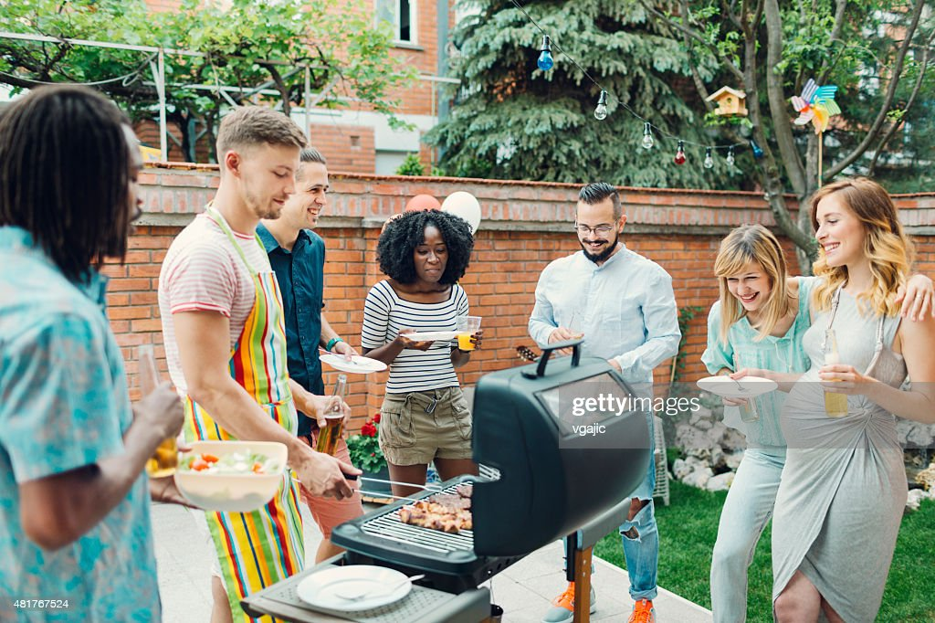 Young People Eating At Barbecue Party. : Stock Photo