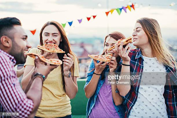 Young people eating pizza on a rooftop party