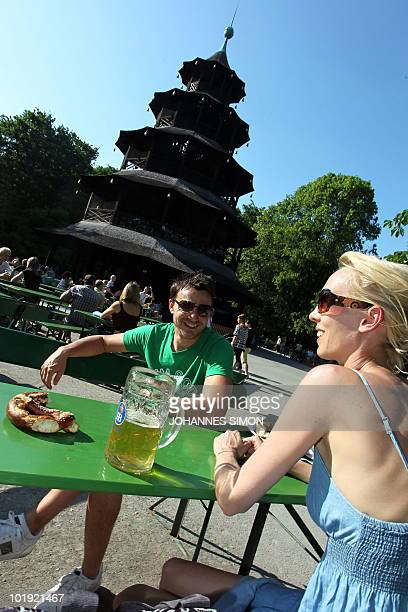 Young people enjoy a beer in the sun in the 'Englischer Garten' beergarden in front of the so called Chinese Tower in the southern German city of...