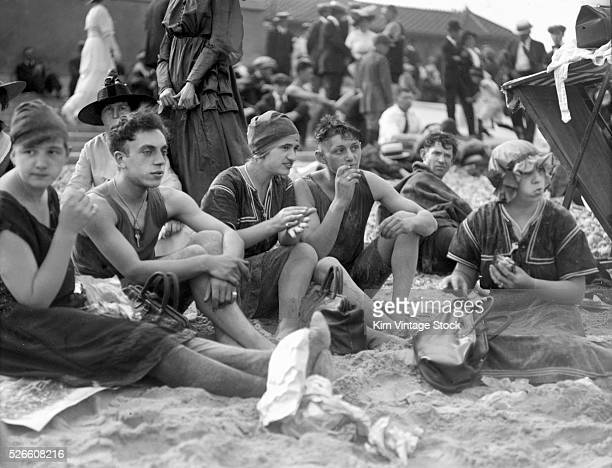 Young people enjoy lunch on the beach together.