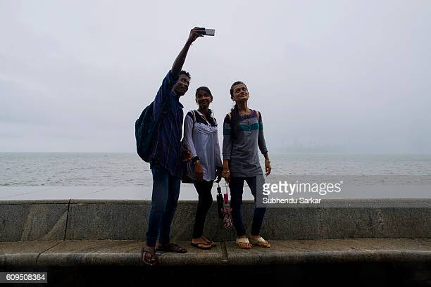 Young people enjoy taking photo with mobile phone at Marine Drive on the coast of Arabian sea during the monsoon season