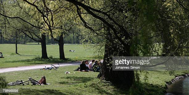Young people enjoy the warm weather under old trees in the world famous Englischer Garten on April 16 in Munich Germany The unseasonably warm weather...