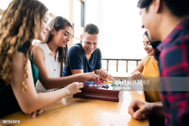 young people enjoyig time with a boardgame - leisure games stock pictures, royalty-free photos & images