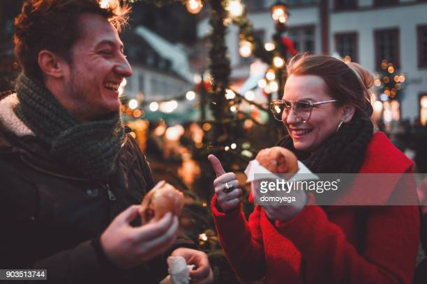 Young people enjoying christmas market food in Germany
