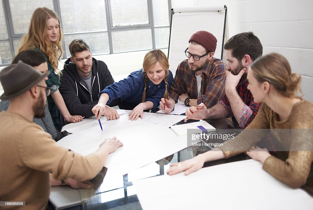 Young people exchanging ideas around a table. : Stock Photo