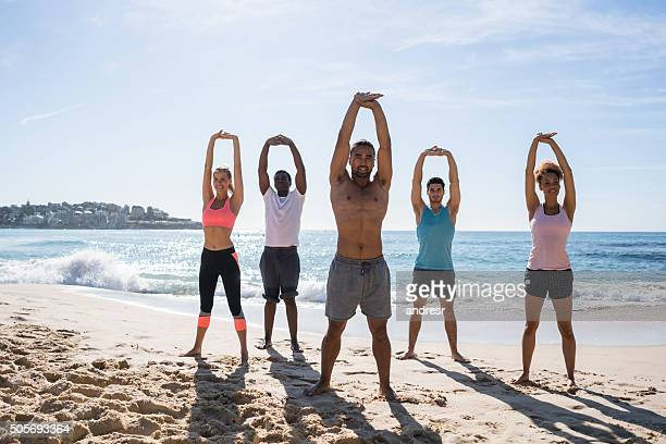Young people exercising at the beach