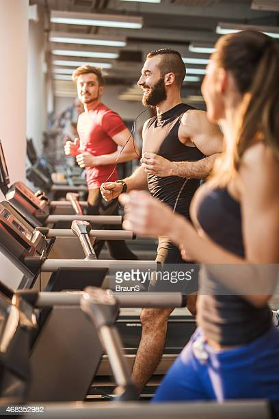 Young people exercising on a treadmill in health club.