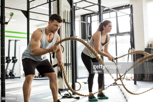 Young people exercising with battle ropes at gym