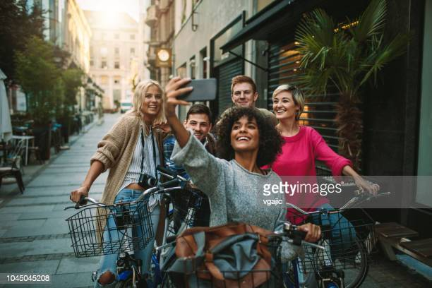 young people exploring the city on bicycles - amicizia foto e immagini stock