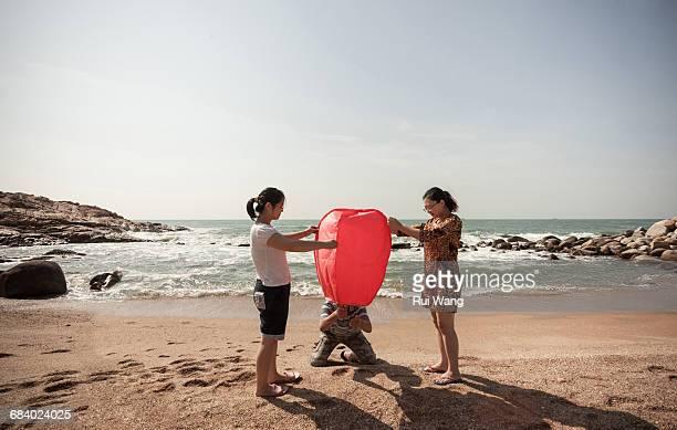 Young people firing sky lantern on the beach