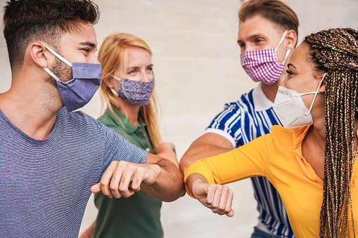 Young people friends bump their elbows instead of greeting with a hug - Avoid the spread of coronavirus, social distance and friendship concept - Focus on right girl eye 1239458181