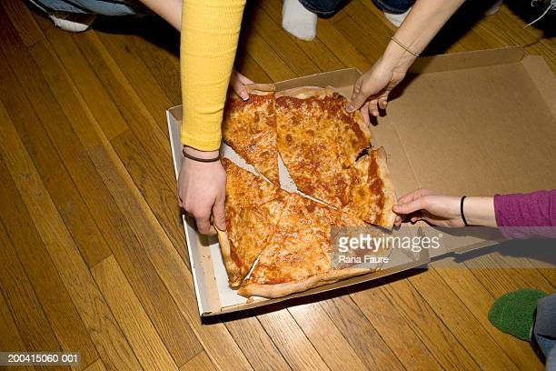 Young people grabbing slices of pizza, elevated view, close-up