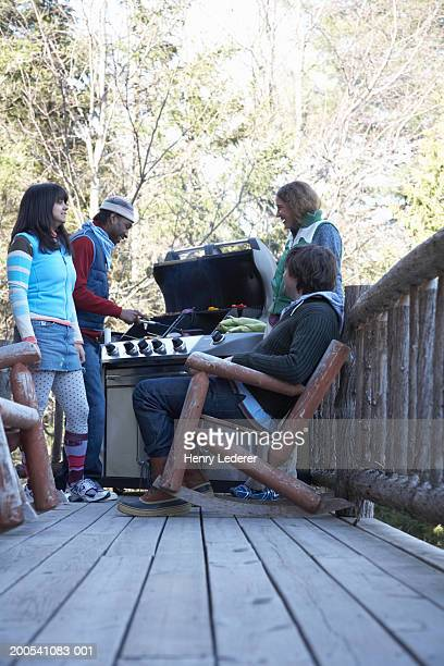 Young people grilling food on porch, winter