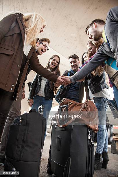 Young people hands together at train station