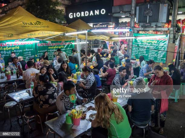 Young people have a diner in a street restaurant
