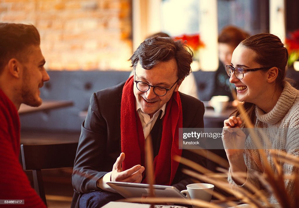 Young people having a business meeting at the coffee bar : Stock Photo