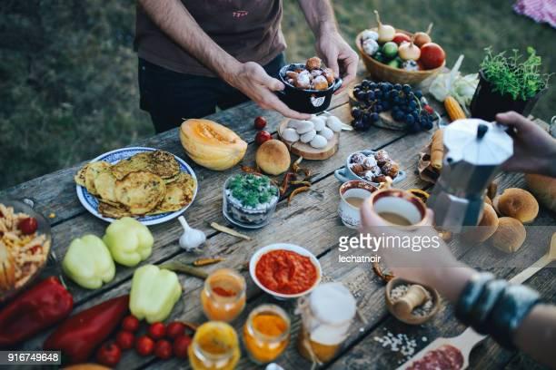 古い木製のテーブルに様々 な健康食品を準備して、屋外のピクニックを持つ若者