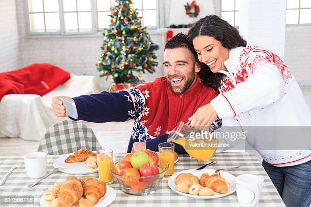 Young people having breakfast at home and making selfie