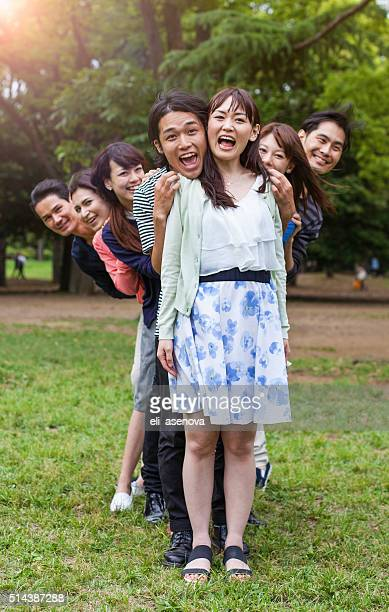 Young people having fun and embrace in city park, Tokyo.