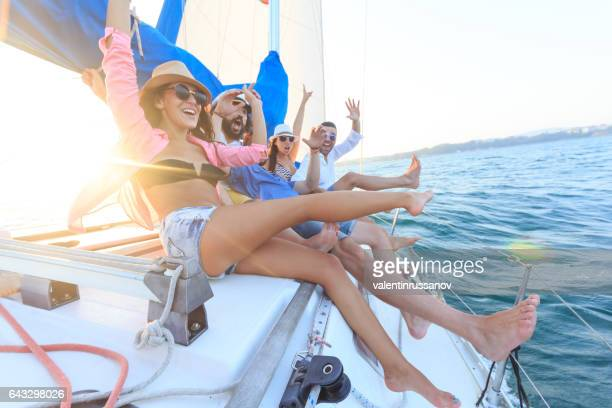 Young people having fun and sailing with yacht