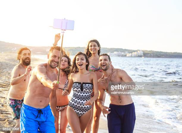 Young people having fun and taking selfie on beach