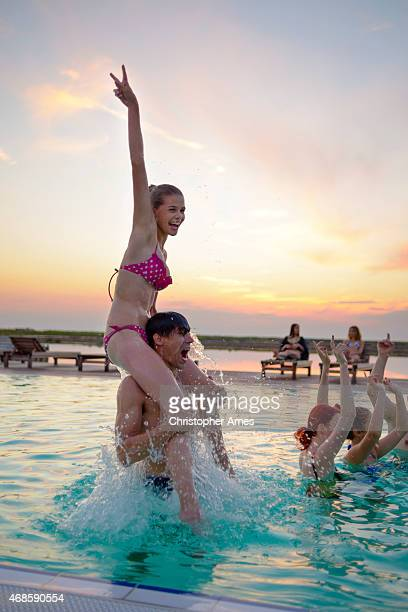 Young People Having Fun in Outdoors Swimming Pool at Sunset
