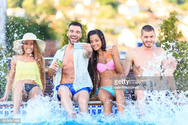 Young people having fun in swimming pool and making selfie