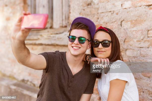 Young people having fun outdoor and making selfie with smart phone against red brick wall. Urban lifestyle, happiness, joy, friends. Instagram