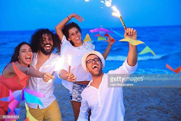 Young people having fun with fireworks and decoration on beach