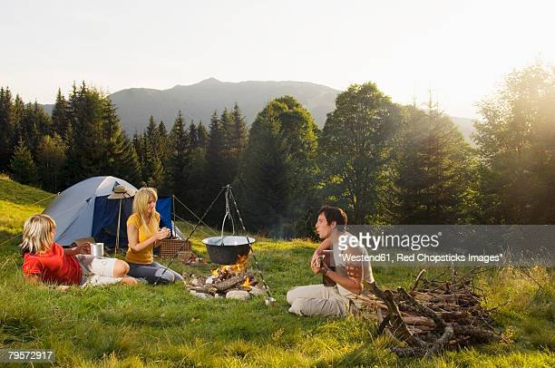 'Young people having picnic, man playing guitar'