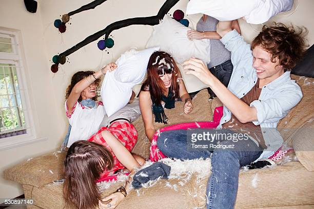 Young people having pillow fight on sofa