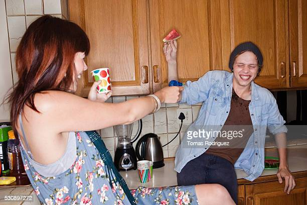 Young people having water fight in kitchen