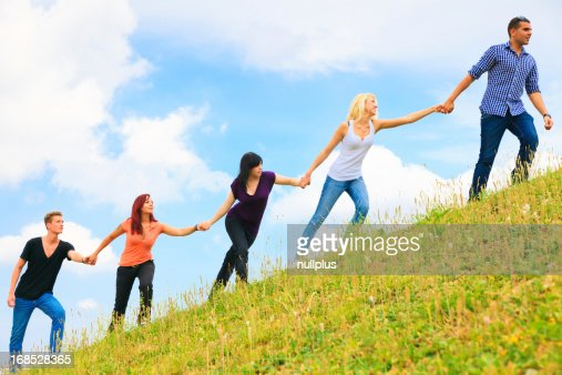 People Helping Each Other: Young People Helping Each Other Climb A Hill Stock Photo